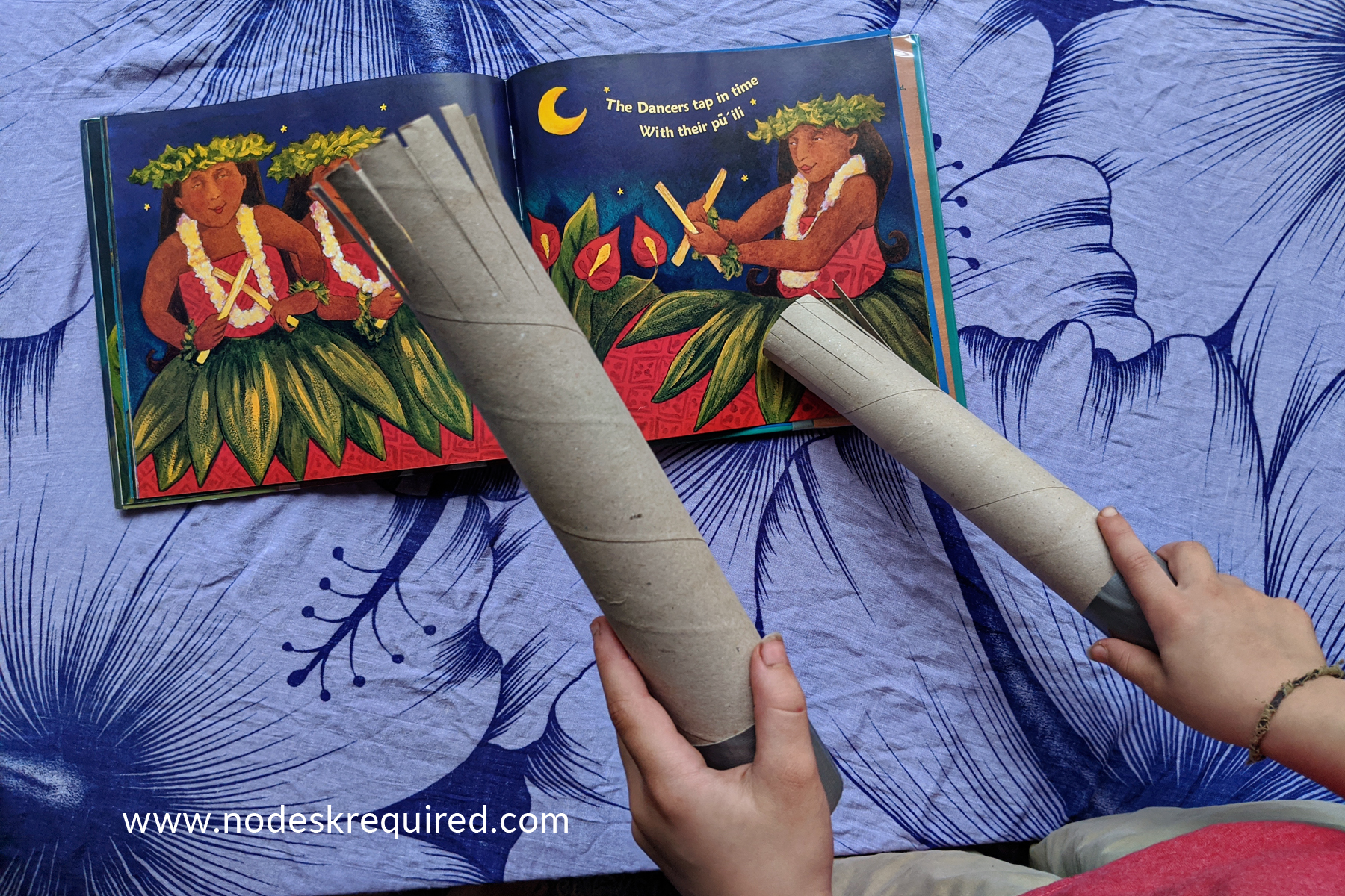 playing cardboard tube pu'ili Hawaiian rhythm sticks on open Hula Lullaby book
